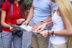 Touriste trois regardant la carte dans la rue Photos libres de droits