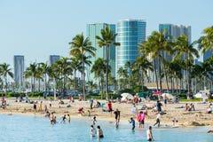 Touristen auf beschäftigtem Strand von Waikiki Stockfotografie