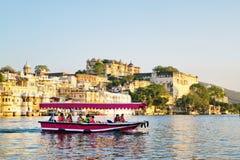 Touristen auf dem Boot, das Udaipur See Pichola-Sonnenuntergangboot nimmt, fahren mit Stadt-Palast auf Hintergrund Stockfoto