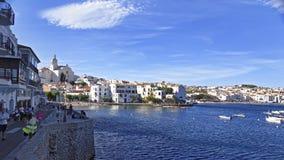 Touristen auf dem Kai und der Ansicht von Cadaques beherbergten im Sommer lizenzfreie stockbilder