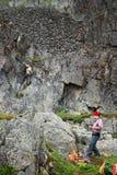 Touristen auf einem Halt unter der bloßen Klippe Lizenzfreie Stockfotografie