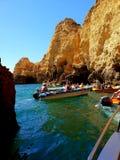 Touristen auf kleinen Booten die vielen H?hlen und die Grotte erforschend punktiert um die K?ste von Lagos, Portugal lizenzfreie stockbilder