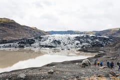 Touristen auf Wanderweg zu Solheimajokull-Gletscher Lizenzfreie Stockbilder