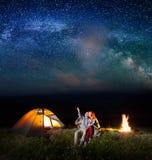 Touristen beim Kampieren nachts gegen sternenklaren Himmel Stockfoto