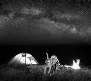 Touristen beim Kampieren nachts gegen sternenklaren Himmel stockbild