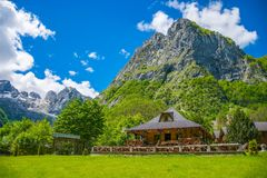 Touristen besichtigten das Restaurant, das auf der Ebene zwischen den Hoch Schnee-mit einer Kappe bedeckten Bergen ist Stockfotografie