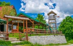 Touristen besichtigten das Restaurant, das auf der Ebene zwischen den Hoch Schnee-mit einer Kappe bedeckten Bergen ist Stockbilder