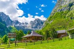 Touristen besichtigten das Restaurant, das auf der Ebene zwischen den Hoch Schnee-mit einer Kappe bedeckten Bergen ist Stockfotos
