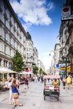 Touristen bilden auf der ganzen Erde Wege unter einer der Hauptstraßen, Kartner Strasse in Wien, Österreich. Stockbild