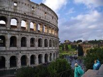 Touristen in den Regenmänteln nahe dem Kolosseum in Rom, Italien Stockfoto
