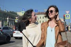 Touristen der jungen Damen machen selfies an einer Br?cke in St Petersburg, Russland und haben Spa? vor Kamera lizenzfreies stockfoto