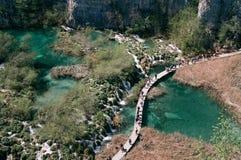 Touristen, die ?ber T?rkiswasser von Plitvice Seen gehen lizenzfreies stockbild