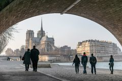 Touristen, die auf die Banken von der Seine unter die Brücke Alexandre III mit der Notre Dame-Kathedrale im Hintergrund schlende stockfotografie