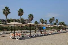Touristen, die auf dem privaten Strand der Ruhesessel im Mittelmeererholungsort liegen Lizenzfreies Stockbild