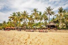 Touristen, die auf dem Sand eines tropischen Strandes ein Sonnenbad nehmen Stockbilder