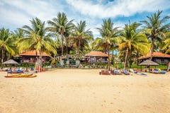 Touristen, die auf dem Sand eines tropischen Strandes ein Sonnenbad nehmen Stockfotos