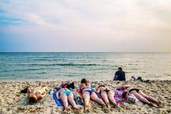 Touristen, die auf dem Sand eines tropischen Strandes ein Sonnenbad nehmen Stockfotografie