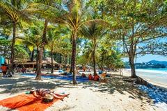 Touristen, die auf dem Sand eines tropischen Strandes im Schatten ein Sonnenbad nehmen Stockfoto