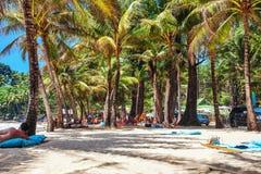 Touristen, die auf dem Sand eines tropischen Strandes im Schatten ein Sonnenbad nehmen Stockfotografie