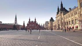 Touristen, die auf den Roten Platz nahe dem Kreml und dem GUMMIkaufhaus an einem sonnigen Tag gehen Stockfotografie