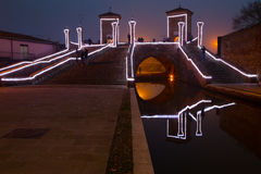 Touristen, die auf die Brücke Trepponti, Comacchio, Italien bis zum Nacht gehen Stockbilder