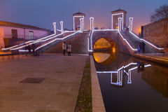 Touristen, die auf die Brücke Trepponti, Comacchio, Italien bis zum Nacht gehen Stockfotografie