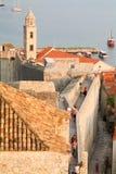 Touristen, die auf die Stadtmauern von Dubrovnik gehen Lizenzfreies Stockfoto