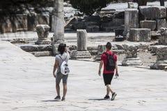 Touristen, die auf eine Straße der antiken Stadt von Ephesus gehen Lizenzfreie Stockfotografie