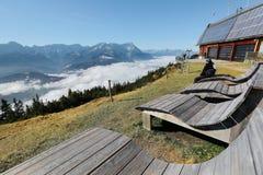 Touristen, die auf einer Holzbank, den Panoramablick des Berges Zugspitze genießend sitzen Stockbild