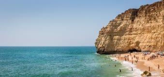 Touristen, die auf sandigem Strand in Portugal sich entspannen Lizenzfreie Stockfotografie