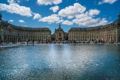 Touristen, die den Platz de la Bourse gesehen vom Boulevard mit in Front der Spiegelbrunnen besichtigen: ` Mirroir d Eau stockfotografie