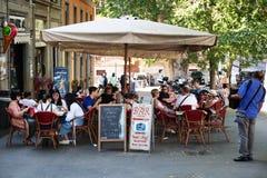 Touristen, die an den Stangen einer Stange in der Stadt sitzen Lizenzfreies Stockbild