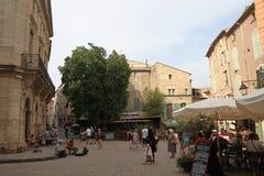 Touristen, die in den zentralen Platz der französischen Stadt von Pezenas, Frankreich schlendern Lizenzfreie Stockfotos
