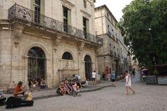 Touristen, die in den zentralen Platz der französischen Stadt von Pezenas, Frankreich schlendern Lizenzfreie Stockbilder