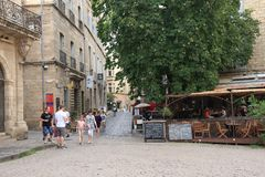 Touristen, die in den zentralen Platz der französischen Stadt von Pezenas, Frankreich schlendern Lizenzfreies Stockfoto