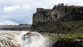 Touristen, die Dettifoss, den stärksten Wasserfall in Island besuchen Lizenzfreie Stockbilder