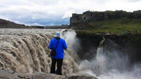 Touristen, die Dettifoss, den stärksten Wasserfall in Island besuchen Stockfotos