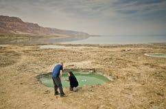 Touristen, die Drecklöcher in der Wüste betrachten Stockfoto