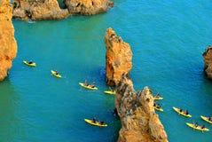 Touristen, die durch die großartigen Felsformationen Kayak fahren Stockbild