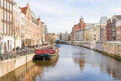 Touristen, die durch einen Kanal in Amsterdam gehen Stockbild