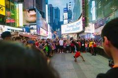 Touristen, die eine Leistung in Time Square, New York genießen Lizenzfreie Stockfotos