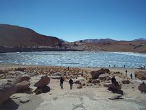 Touristen, die einen gefrorenen Teich in der Wüste besichtigen stockbild