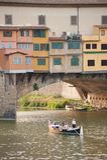 Touristen, die entlang den der Arno-Fluss, nearPonte Vecchio-Brücke segeln Stockfotografie