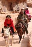 Touristen, die Esel in PETRA Jordanien reiten Lizenzfreie Stockbilder