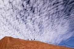 Touristen, die Felsen Uluru Ayers klettern stockbild