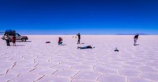 Touristen, die Fotos bei Salar de Uyuni, Bolivien machen lizenzfreies stockfoto