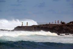 Touristen, die gefährliche Wintermeereswogen aufpassen Stockbild