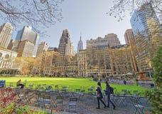 Touristen, die grünen Rasen und Wolkenkratzer in Bryant Park betrachten Lizenzfreies Stockfoto