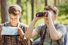 Touristen, die im Wald stehen, durch bino sprechen und schauen stockfoto