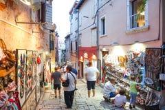 Touristen, die nahe bei angezeigten Andenken in Rovinj gehen Stockbild